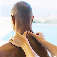 view of a young bald man getting a neck massage Stock Photo - Premium Royalty-Freenull, Code: 618-00467681