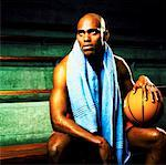 low angle view of a basketball player sitting holding a basketball Stock Photo - Premium Royalty-Free, Artist: Cusp and Flirt, Code: 618-00469095