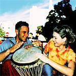 close-up of a couple sitting and beating on a drum; smiling Stock Photo - Premium Royalty-Free, Artist: Ed Gifford, Code: 618-00470076