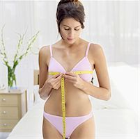 woman measuring her bust with measuring tape Stock Photo - Premium Royalty-Freenull, Code: 618-00487271