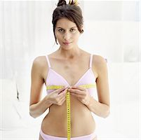 Front view portrait of a young woman measuring her bust with a measuring tape Stock Photo - Premium Royalty-Freenull, Code: 618-00487272