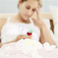 Young woman lying in bed with a cold Stock Photo - Premium Royalty-Freenull, Code: 618-00488880