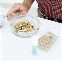 Man standing holding cigarette close to a full ashtray and nicotine pills on a table Stock Photo - Premium Royalty-Freenull, Code: 618-00488991