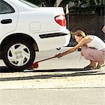 woman placing a car jack under the rear of a car Stock Photo - Premium Royalty-Free, Artist: Minden Pictures, Code: 618-00493954