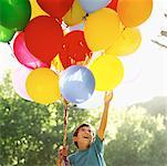 low angle view of a boy holding balloons Stock Photo - Premium Royalty-Free, Artist: Guntmar Fritz, Code: 618-00494539