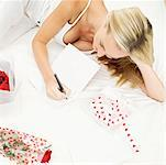 Young woman writing a card lying on bed with a present Stock Photo - Premium Royalty-Free, Artist: Cusp and Flirt, Code: 618-00504814