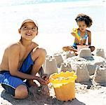 young boy and girl building sandcastles on the beach