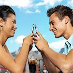 side profile close-up of a young couple sitting across using their mobile phones Stock Photo - Premium Royalty-Free, Artist: Rick Gomez, Code: 618-00509608