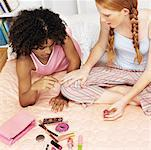 two young girls sitting on bed with cosmetics and applying nail polish