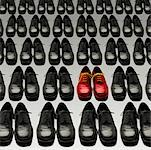 Red Shoes Among Rows of Black Shoes
