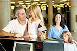 Man Buying Airplane Ticket with Daughter    Stock Photo - Premium Rights-Managed, Artist: Pete Webb, Code: 700-00526577