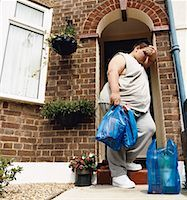 Overweight Man Stands at His Front Door With Carrier Bags of Groceries Leaning His head on His Arm Stock Photo - Premium Royalty-Freenull, Code: 613-00535235