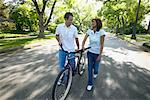 Couple Walking with Bicycle, Down Street