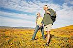 Couple Hiking Through Wildflowers    Stock Photo - Premium Rights-Managed, Artist: Peter Griffith, Code: 700-00552502