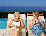 Women Drinking Tea By Swimming Pool By the Ocean