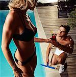 Pool Boy Taking A Drink From A Woman In Bikini    Stock Photo - Premium Rights-Managed, Artist: Masterfile, Code: 700-00606430