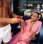 Shirtless Man Giving A Cocktail to A Mature Woman