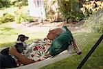 Mature Man Napping In Hammock With Dog    Stock Photo - Premium Rights-Managed, Artist: Steve Prezant, Code: 700-00609188