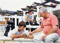 Grandfather and Grandson Playing Chess Stock Photo - Premium Rights-Managednull, Code: 700-00610216