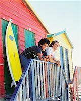 Friends by Beach Hut with Surfboard    Stock Photo - Premium Rights-Managednull, Code: 700-00623336