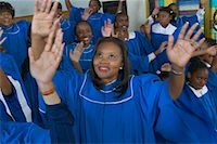 Congregation of Gospel Singers With Raised Hands Singing in a Church Service Stock Photo - Premium Royalty-Freenull, Code: 613-00624653