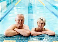 seniors woman in swimsuit - Smiling Senior Couple Leaning on the Side of a Swimming Pool Stock Photo - Premium Royalty-Freenull, Code: 613-00624755