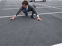 Businessman Crouching in Parking Lot    Stock Photo - Premium Rights-Managednull, Code: 700-00644017