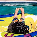 Boy Lying on Inner Tube In Swimming Pool    Stock Photo - Premium Rights-Managed, Artist: Mark Peter Drolet, Code: 700-00659649