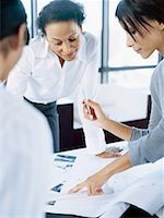 three businesswomen discussing a blueprint in an office Stock Photo - Premium Royalty-Freenull, Code: 618-00663783