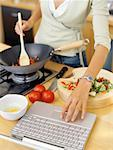 young woman cooking food and using a laptop in the kitchen Stock Photo - Premium Royalty-Free, Artist: Daniel Barillot, Code: 618-00664732
