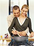 young woman cooking food with a young man embracing her in the kitchen Stock Photo - Premium Royalty-Free, Artist: Ron Fehling, Code: 618-00664741