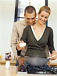 young woman cooking food with a young man embracing her from behind in the kitchen Stock Photo - Premium Royalty-Free, Artist: Masterfile, Code: 618-00664750