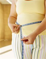 mid section view of a woman measuring her waist Stock Photo - Premium Royalty-Freenull, Code: 618-00668994