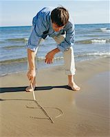 Man Drawing Dollar Sign on the Sand    Stock Photo - Premium Rights-Managednull, Code: 700-00686814