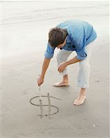 Man Drawing Dollar Sign on the Sand    Stock Photo - Premium Rights-Managednull, Code: 700-00686815