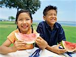 portrait of a sister and her brother eating slices of watermelon Stock Photo - Premium Royalty-Freenull, Code: 618-00689395