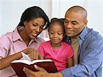 parents and their daughter reading the bible