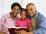 portrait of parents and their daughter reading the bible