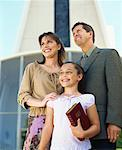 low angle view of parents and their daughter standing in front of a church