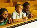 parents and their son praying in church