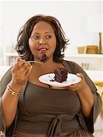 mid adult woman eating a slice of chocolate cake Stock Photo - Premium Royalty-Freenull, Code: 618-00690844