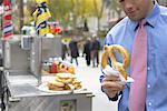 Businessman Eating Soft Pretzel, New York, New York, USA
