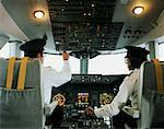 Male and female aeroplane pilot, operating controls, rear view Stock Photo - Premium Royalty-Free, Artist: Multi-bits, Code: 613-00703045