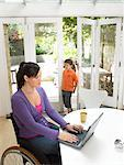 Mother in wheelchair using laptop at table, son (7-9) at garden door Stock Photo - Premium Royalty-Free, Artist: Masterfile, Code: 613-00703609