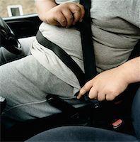Mid-Section of an Overweight Man Fastening a Car Seatbelt Stock Photo - Premium Royalty-Freenull, Code: 613-00707692