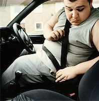 Overweight Man Sits in the Drivers Seat of a Car Looking Down as he Fastens His Seatbelt Stock Photo - Premium Royalty-Freenull, Code: 613-00707693