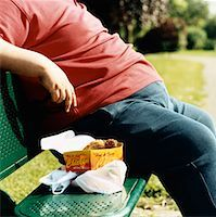 Mid-Section of an Overweight Man Sitting on a Park Bench With Take Away Food Stock Photo - Premium Royalty-Freenull, Code: 613-00707696