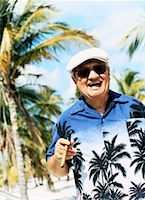 Portrait of a Smiling Senior Man Wearing a Hawaiian Shirt and Smoking a Cigar Stock Photo - Premium Royalty-Freenull, Code: 613-00710157