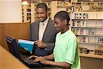 Librarian helping boy use computer Stock Photo - Premium Royalty-Free, Artist: Marie Blum, Code: 604-00754390
