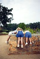 Girls looking over wall Stock Photo - Premium Royalty-Freenull, Code: 604-00757380